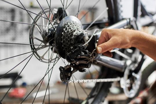 Cropped shot of professional mechanic working in bicycle repair shop, worker repairing bike using special tool
