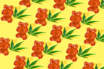Pattern gummies in form of a bear with CBD oil on a yellow background. Minimum CBD concept