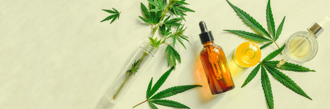 Various glass bottles with CBD oil, THC tincture and hemp leaves on a marble background. Flat lay, minimalism. Cosmetics CBD oil.