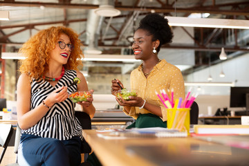 Curly businesswoman eating salad with dark-skinned colleague