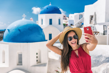 Fototapete - Europe luxury travel destination Santorini cruise tourist Asian woman having fun taking self portrait photo with mobile phone at famous three blue domes church in Oia, Greece.