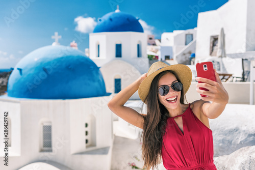 Wall mural Europe luxury travel destination Santorini cruise tourist Asian woman having fun taking self portrait photo with mobile phone at famous three blue domes church in Oia, Greece.