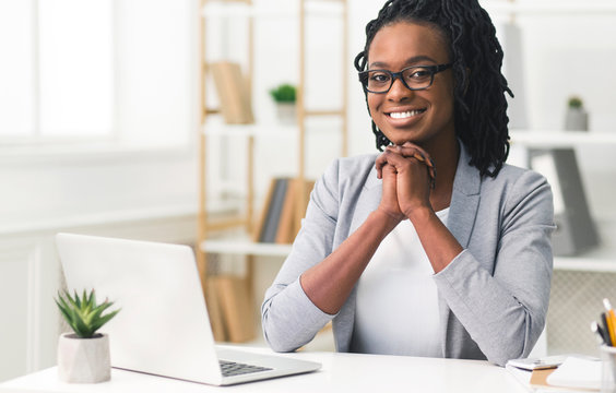 Black Business Girl Smiling At Camera Sitting In Modern Office