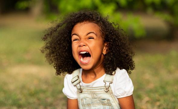 Little girl screaming over natural summer background