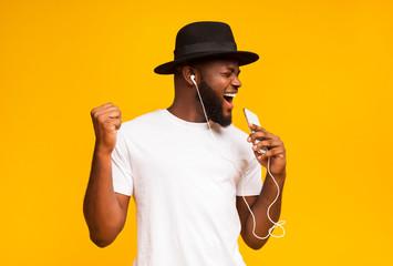 Happy african man in hat singing into smartphone like microphone Fotobehang