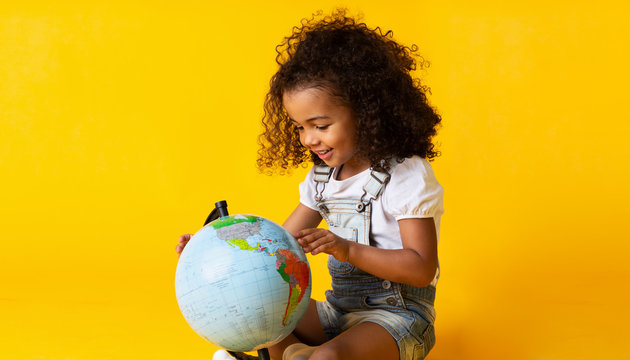 Cute little girl looking at earth globe, yellow background
