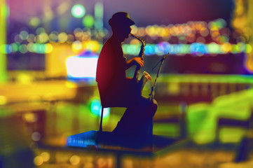 Night saxophonist silhouette on colorful blurred background