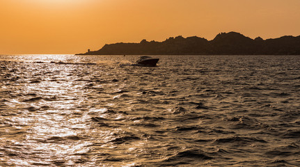 Motor boat on the sea at sunset, in the background the coast at Bonifacio, Corsica, France