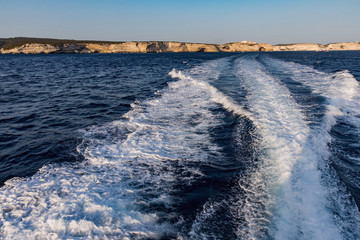 Sail on the sea on a yacht, water stream behind the engine. In the background the coast at Bonifacio, Corsica, France