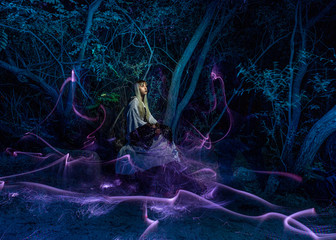 Nocturnal photography, lightpainting, representing a model in the river with shadows made with lanterns on the river.