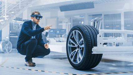 Automotive Engineer Working on Electric Car Chassis Platform, Using Augmented Reality Headset. In...