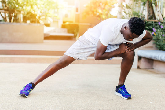 Athletic African American man in blue sneakers doing stretching exercise while training in park on sunny day