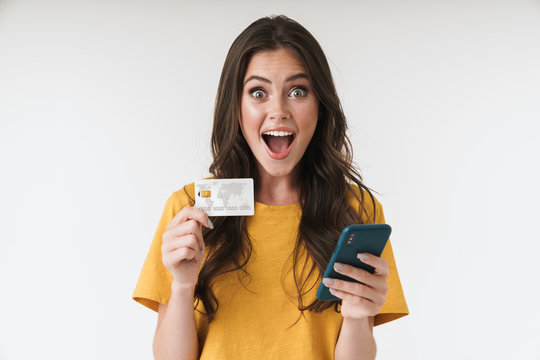 Image of beautiful brunette woman wearing casual clothes holding credit card and cellphone