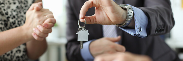 Hand of realtor hold house key aganist office background. Family new apartment credit concept.