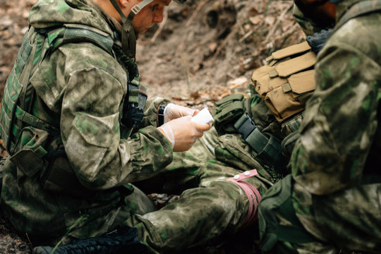 Bandaging a wounded soldier. A group of soldiers in defense of their positions.
