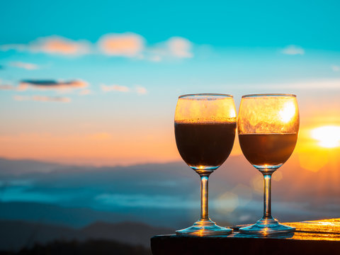 Red wine glass with the sunrise overlooking the mountains background.