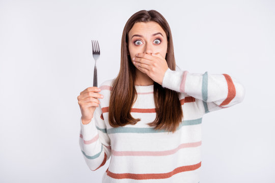 Crazy lady hiding mouth with arm remind herself about taboo on night eating wear striped pullover isolated white background