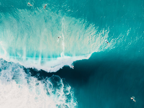 Aerial view of surfing at barrel waves. Blue wave in ocean and surfers