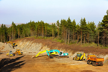 Heavy-duty construction machines at construction site, high in the mountain.