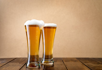 Two light beer glasses w on the light yellow background