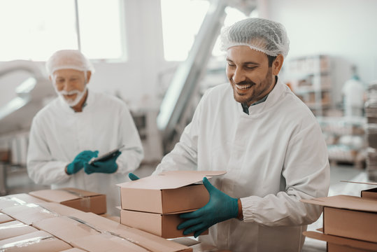 Smiling hardworking dedicated Caucasian employee arranging boxes while his superior using tablet and checking on him. Both are dressed in white sterile uniforms. Food plant interior.