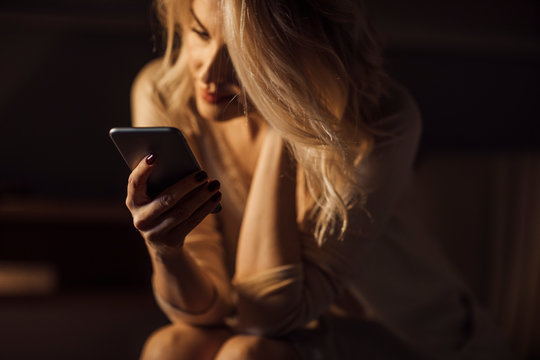 Young blonde woman holding smart phone