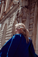 Walk through historic center. A beautiful girl, in a blue jacket against background of historic buildings, leads along.