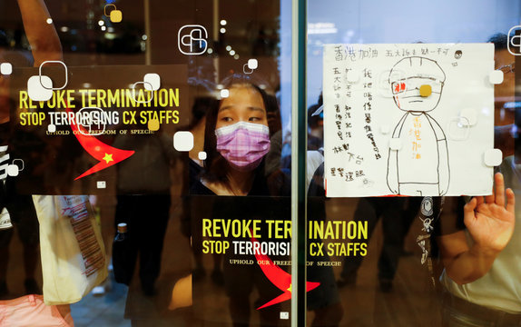 People paste placards on windows as they take part in a rally held by the Hong Kong Confederation of Trade Unions after a number of crew members in the aviation industry were let go for joining the anti-extradition bill protests, in Hong Kong