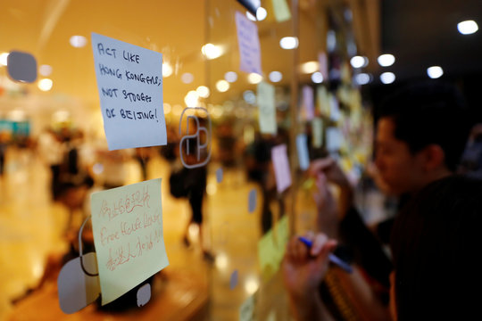 People write messages on post-it notes as they take part in a rally held by the Hong Kong Confederation of Trade Unions after a number of crew members in the aviation industry were let go for joining the anti-extradition bill protests, in Hong Kong