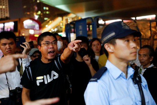 People react over the presence of police during rally held by the Hong Kong Confederation of Trade Unions after a number of crew members in the aviation industry were let go for joining the anti-extradition bill protests, in Hong Kong