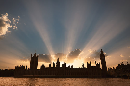 Dramatic sun beams behind the Palace of Westminster as the sun sets in London.