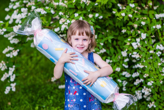 4 years old girl hugs big candy. Photo session in the garden.