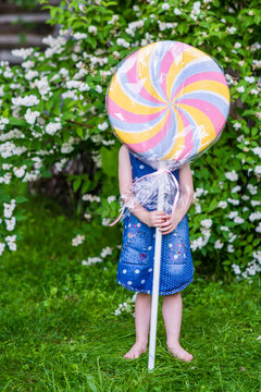 4 years old girl hide behind the big lollypop. Photo session in the garden.