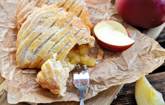 Easy Apple Turnovers (German name is Apfeltaschen) on brown paper with fresh red apples on wooden board and wooden floor.