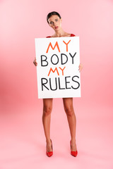 Full length image of upset serious woman wearing white sexual lace lingerie holding placard with text