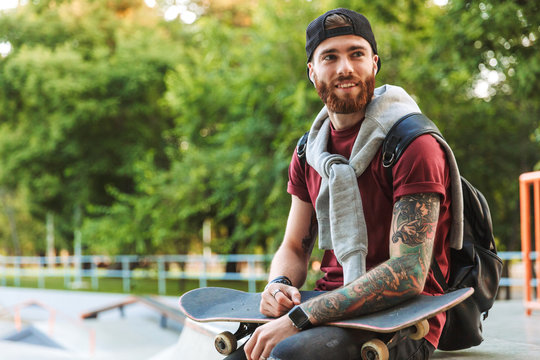 Attractive cheerful young man sitting at the skate park ramp
