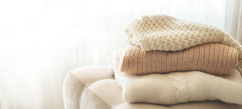 A stack of knitted sweaters in the interior of the living room. The concept of autumn winter comfort