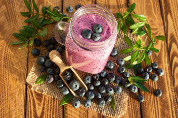 Blueberry dessert or blueberries smoothie with fresh berry on wooden background. Top view.