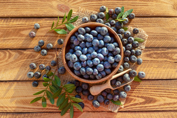Pile and bowl with fresh blueberries on wooden background. Top view.