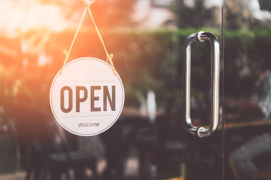 Open sign hanging front of cafe with colorful bokeh light abstract background.