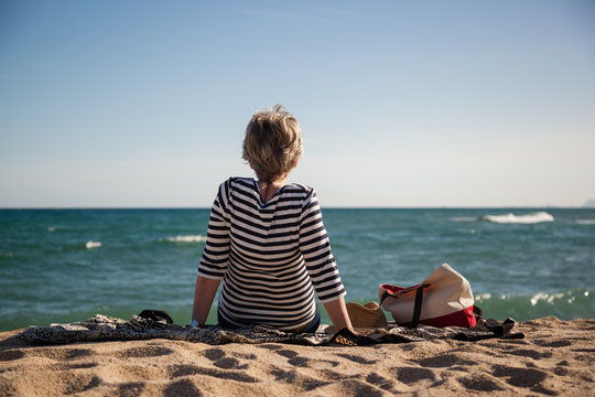 Middle aged woman sitting on the beach watching the sea, back-view