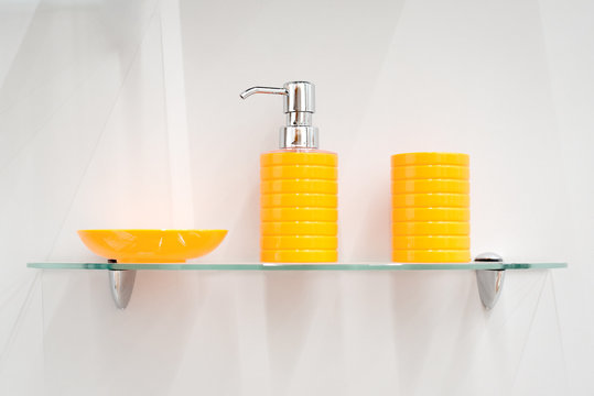 Bathroom accessories on the glass shelf in a bath on a gray background.