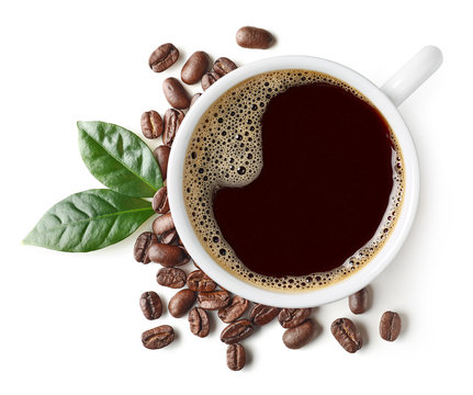 Cup of black coffee with beans and leaves