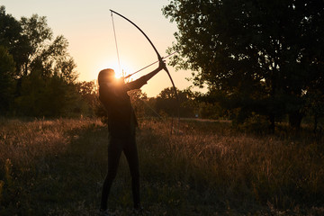A woman shoots a bow in nature at sunset. Wall mural