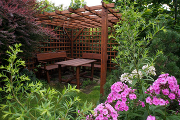 Obraz Drewniana altana ogrodowa w otoczeniu roślin i kwiatów - fototapety do salonu