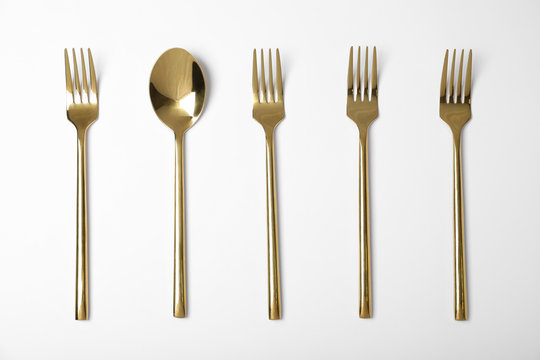 Set of new gold cutlery on white background, top view