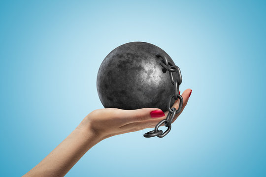 Side closeup of woman's hand facing up and holding black ball and chain on light blue gradient background.