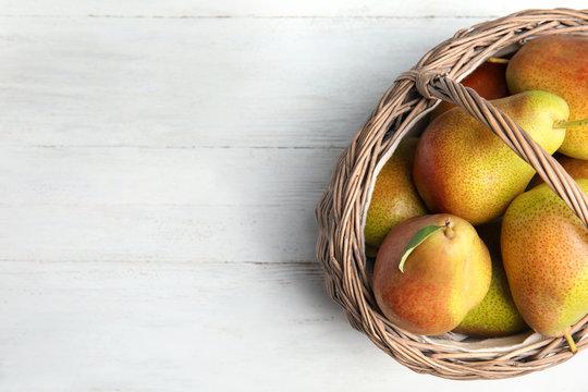 Ripe juicy pears in wicker basket on white wooden table, top view