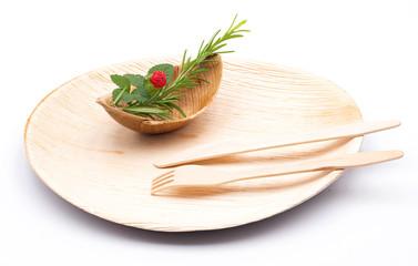 Teller aus Palmblatt und Schale mit Besteck aus Holz