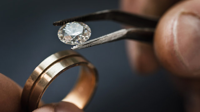 Jeweler craftsman selects a gem for a future gold ring, close-up